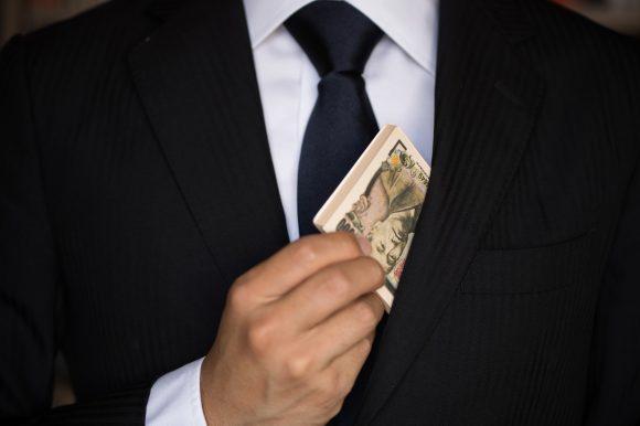 サラリーマンが副業して得た札束を出しているイメージ